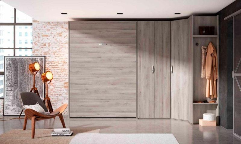 Dormitorio de matrimonio pequeño con cama abatible vertical y armario en acabado madera